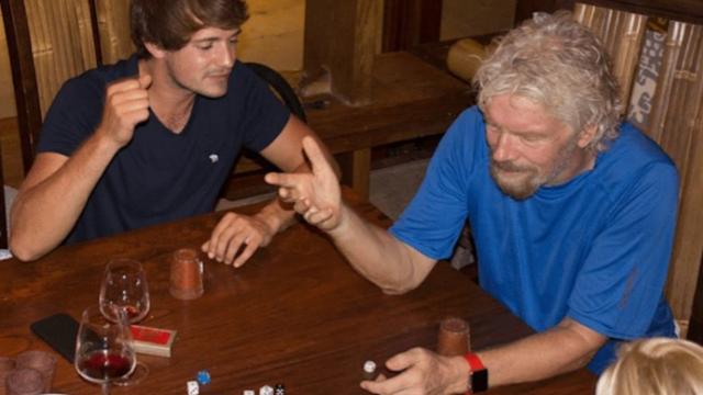 Branson y sus huéspedes jugando a los dados y tomando vino mientas pasa el huracán