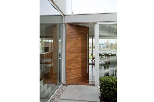 Para entrar en esta casa, se atraviesa un patio exterior que anticipa los materiales y colores que se encontrarán también adentro.