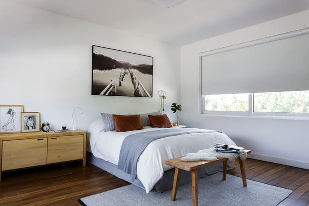 El dormitorio, con piso de incienso, tiene ropa de cama (Du Sud) en combinación de tonos neutros y una cómoda (Encaja Muebles) a modo de mesita de luz con velador (Ikea). La disposición de la alfombra de lana (Mihran) amplía el espacio.  Foto:Living /Daniel Karp