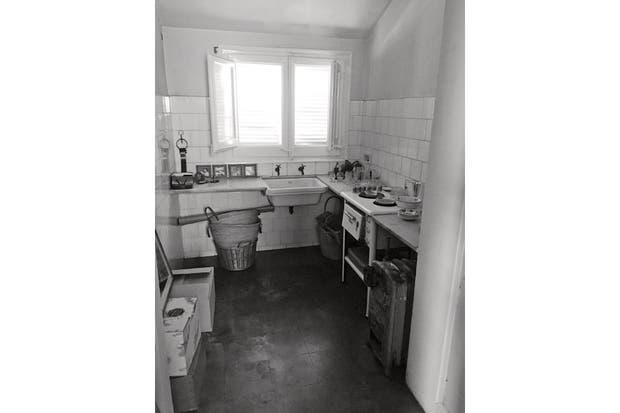 La cocina tipo pasillo estaba prácticamente en ruinas, sin muebles, con revestimiento de azulejos y piso cerámico oscuro. .