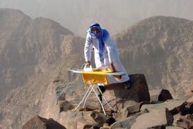 Un alpinista planchando en la cima de una montaña