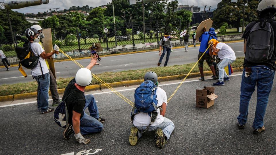 Manifestantes usan una gomera gigante contra la policía antidisturbios en Caracas. Foto: Reuters / Marco Bello