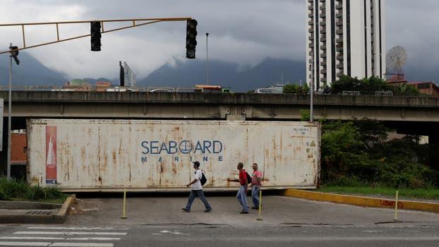 Los abuelos marchan en Venezuela para protestar contra el gobierno, Caracas amaneció con la sorpresa de varios contenedores cortando el paso de los puentes del río para que no puedan cruzar de una zona a otra. Foto: Reuters / Marco Bello