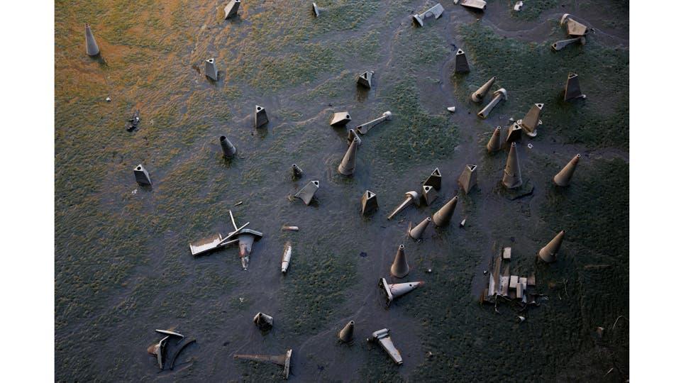 Conos de tráfico se ven en la orilla del río Támesis durante la marea baja