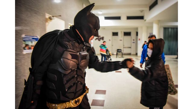Batman saluda a un chico mientras sale del hospital