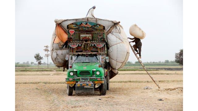 Los trabajadores cargan paja en un camión decorado fuera de Faisalabad