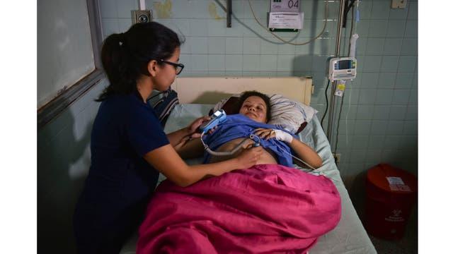 Una trabajadora de la salud monitorea a Joselis Canas de Venezuela mientras espera su fecha de parto en el Hospital Universitario Erasmo Meoz en Cucuta