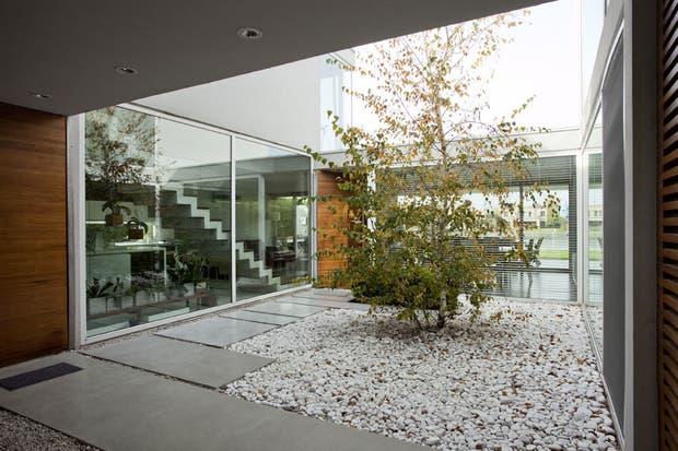 Dos enormes paneles de vidrio dejan ver una escalera de líneas rectas y limpias y la sala de estar, que es el corazón de la casa.