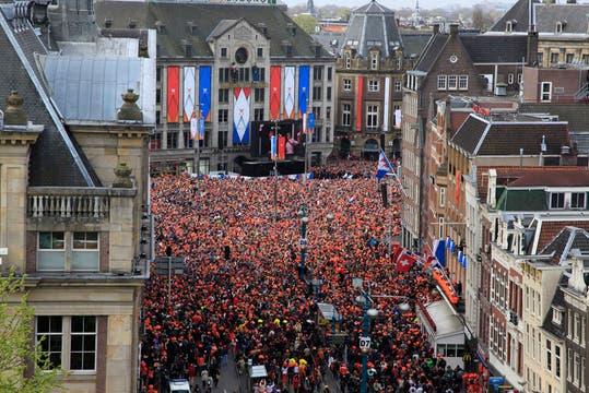 Con carteles y disfraces alusivos a la dinastía Orange, una multitud se congregó en la céntrica plaza Dam para darle la bienvenida a los nuevos reyes. Foto: AP