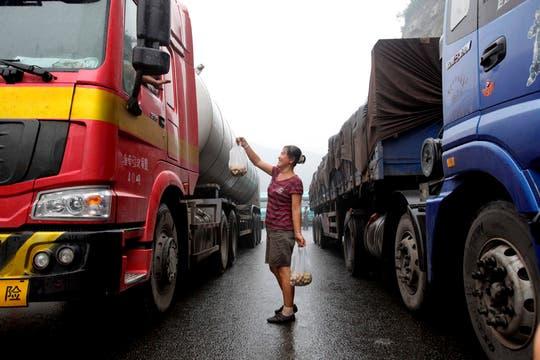 Un vendedor ambulante ofrece comida a los camioneros atrapados en el interminable embotellamiento de tránsito. Foto: EFE