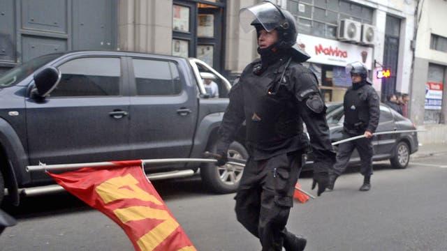 Dos policías recorren las calles laterales con banderas que le quitaron a las agrupaciones manifestantes