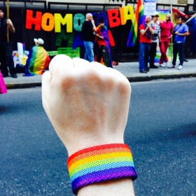 Gene fotografió su propio puño, con una pulsera de la diversidad, frente a la embajada rusa