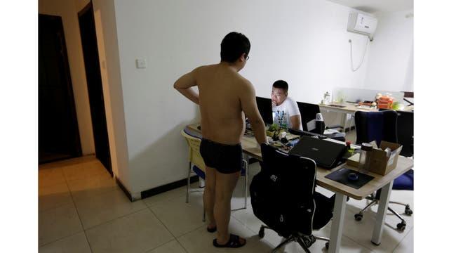 Zhang Huichao, un programador en N-Wei Technology Company Limited, conversa con su colega Yan Xiaolong antes de irse a dormir, en la sala de estar de un apartamento que también se utiliza como oficina