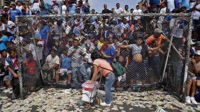 Un vendedor de gelatina aprovecha una pausa en el campeonato de fútbol callejero el Porvenir en Lima, Perú