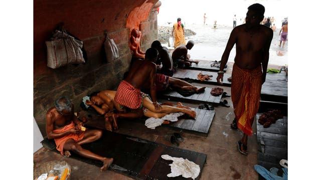 La gente recibe un masaje tradicional bajo un puente en las orillas del río Ganges en Kolkata