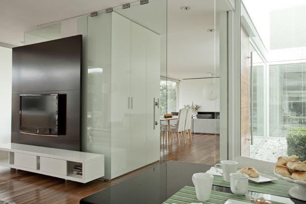 La puerta de vidrio detrás del mueble de la TV comunica con el living y el comedor..