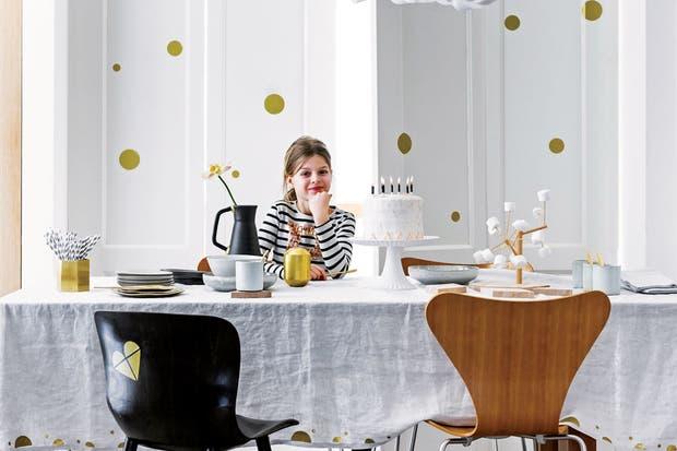 Blanco luminoso y pocos colores que se concretan en formas de diseño. Los vinilos en la pared y la silla no necesitan más sofisticación que el dorado: el juego queda claro.  Foto:Living /Sjoerd Eickmans