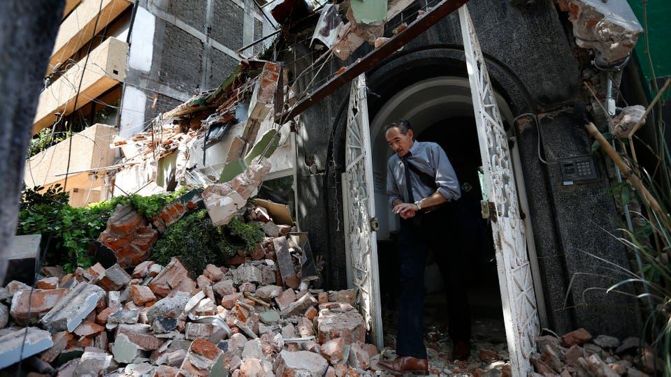Un hombre camina fuera de un edificio colapsado. Foto: AP / Marco Ugarte