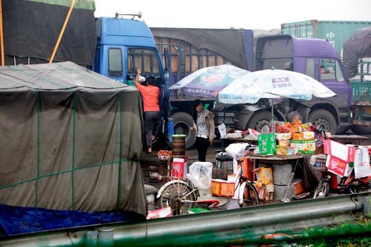 Vendedores ambulantes aprovechan para vender comida a los conductores que ya llevan varios días atascados en la autopísta que lleva a Beijing. Foto: EFE