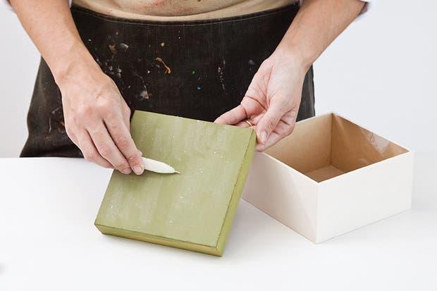 1. Con la pinceleta, sellar con látex blanco la caja y la corona. Dejar secar y lijar muy bien. Después, con la ayuda de la pinceleta, pintar con acrílico verde la tapa y con acrílico blanco antiguo la base. Al final, frotar sobre la tapa una vela.