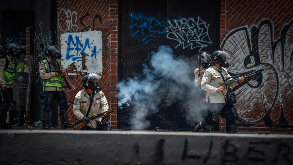 Un policía dispara gas lacrimógeno a los manifestantes. Foto: AFP / Juan Barreto