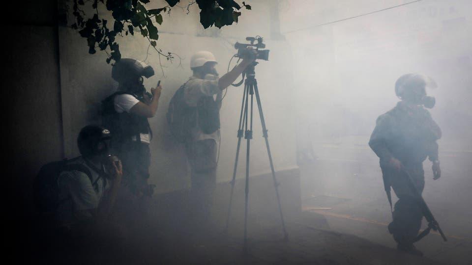 Los medios de comunicación que cubren los disturbios se ponen a resguardo. Foto: Reuters / Carlos Garcia Rawlins