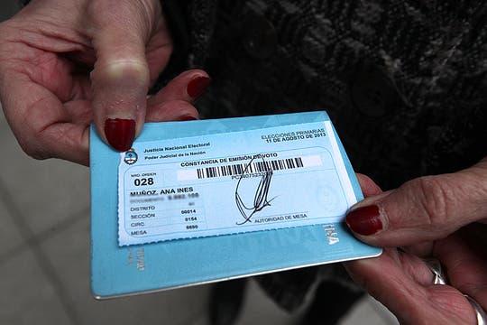 Una mujer muestra el troquel que le entragron luego de votar. Foto: LA NACION / Ezequiel Muñoz
