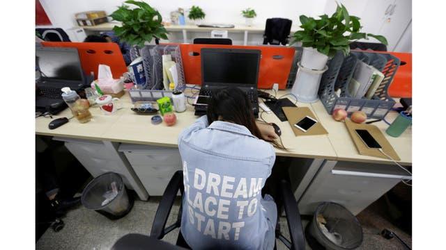Yang Juan, un empleado de Gopal Grupo, toma una siesta en su asiento después del almuerzo