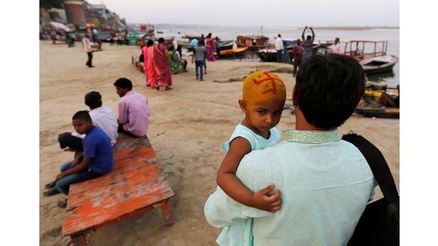 Un devoto hindú lleva a su hija después de una ceremonia religiosa a orillas del río Ganges en Varanasi
