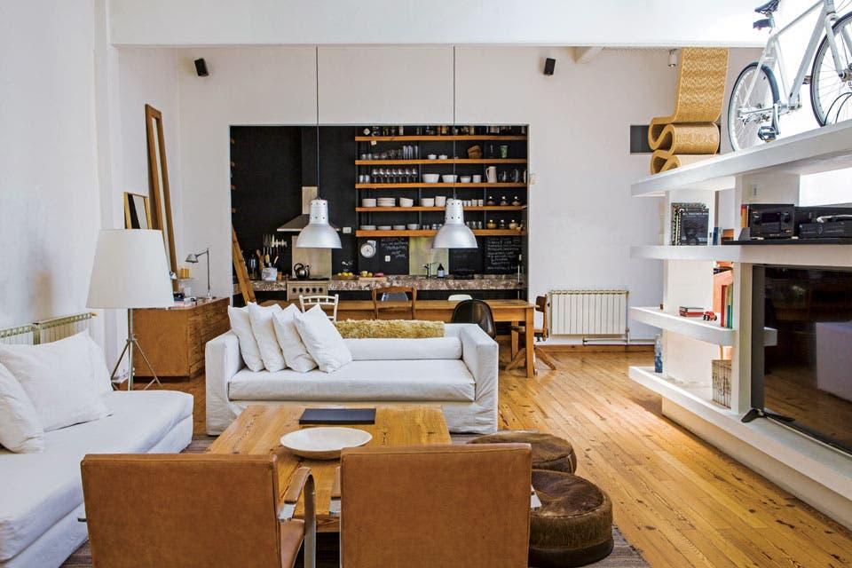 Una estantería blanca actúa como divisor semitransparente entre el área social y la suite, además de alojar el televisor, libros, revistas y discos. En el estante superior, la livianísima bicicleta sin cadena que usa Martín y una silla 'Wiggle', obra del arquitecto Frank Gehry.  Foto:Living /Santiago Ciuffo