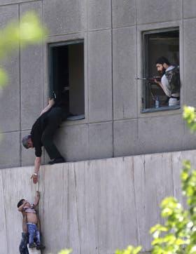 Las fuerzas de seguridad evacuan a un chico en el Parlamento iraní