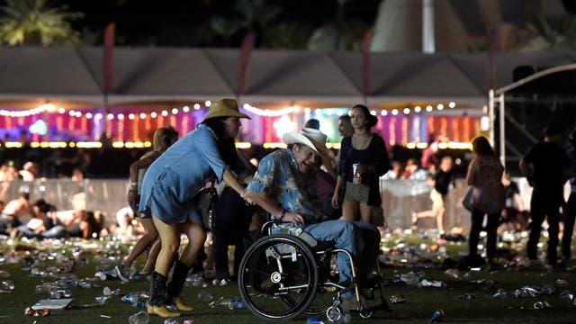 Una mujer asiste a un hombre en silla de ruedas luego del feroz tiroteo durante el recital