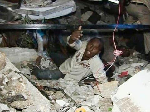 Un hombre pide ayuda mientras se encuentra atrapado entre los escombros.. Foto: Reuters
