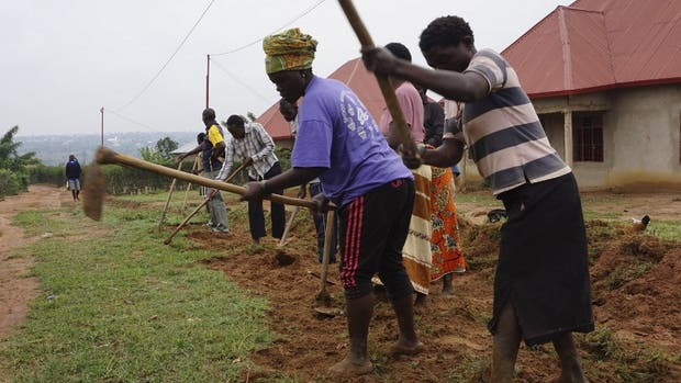 Aldeanos trabajan sobre un drenaje de Mbyo, donde genocidas y víctimas viven lado a lado