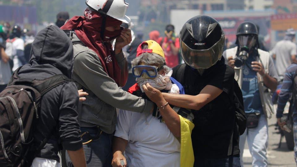 Dos manifestantes asisten a una señora alcanzada por los gases. Foto: Reuters / Marco Bello