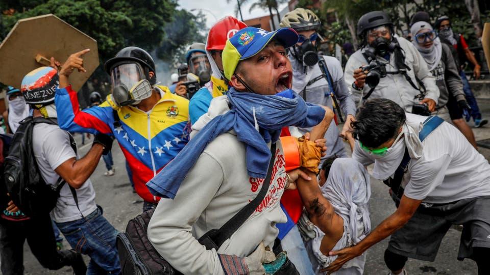 Manifestantes ayudan a un herido durante una manifestación en Caracas. Foto: Reuters / Carlos Garcia Rawlins