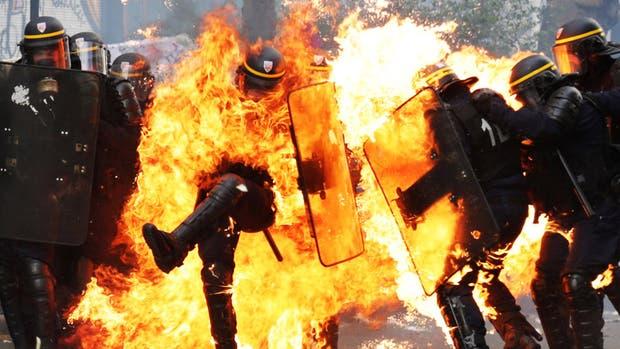 París: un policía antidisturbios queda envuelto en llamas después de que un grupo de manifestantes encapuchados arrojaron bombas molotoven cercanías a la Plaza de la Bastilla