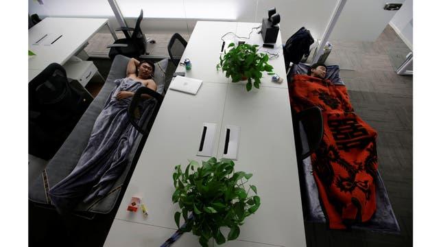 Han Liqun (a la izquierda) de Renren crédito Management Co.,duerme junto al ingeniero Xiang Siyang en camas de campaña en la oficina después de terminar el trabajo temprano en la mañana