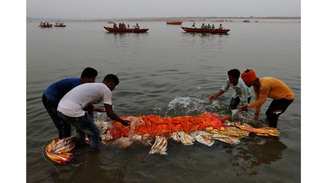 Los parientes sumergen un cuerpo en el río Ganges antes de la cremación en Varanasi