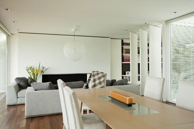Mesa de madera clara con vidrio central y juego de sillas blancas de respaldo alto. La persiana americana es ideal para echar un vistazo al patio exterior que comunica con la calle.