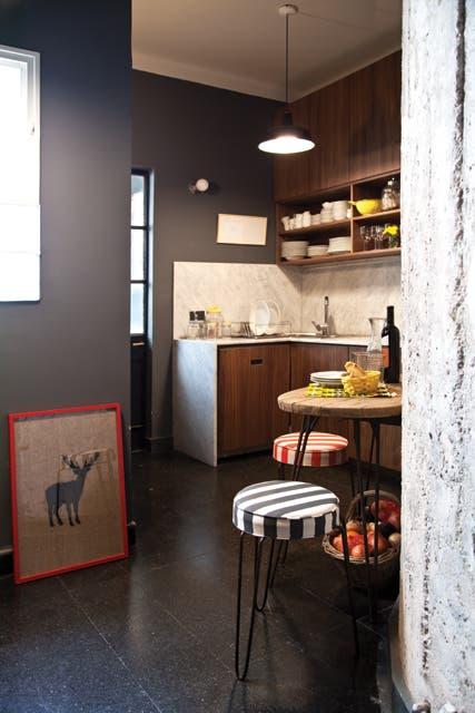 Para la cocina se optó por muebles enchapados en nogal italiano con mesada y alzada en mármol de Carrara y una lámpara industrial negra.  Foto:Living /Magalí Saberian