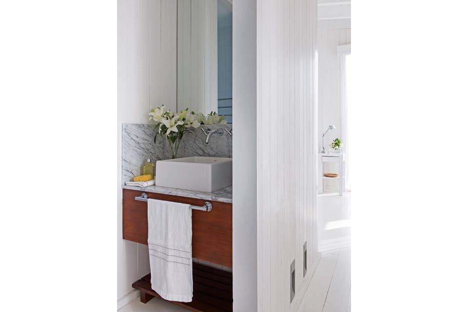 En el baño con resvestimiento en mármol de Carrara, toalla de hilo (Materia).  Foto:Living /Gentileza Enrique Menossi