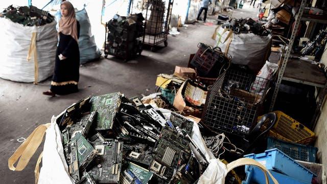Una mujer camina por un centro de reciclado de basura electrónica en Kuala Lumpur
