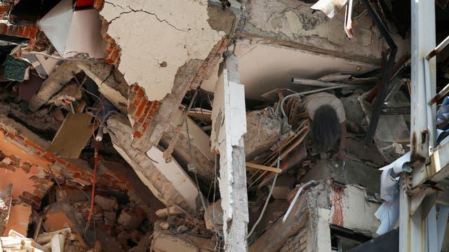 El cuerpo de una mujer entre los escombros de un edificio colapsado. Foto: AP / Marco Ugarte
