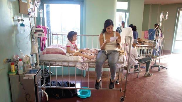 Ashley, una niña de 3 años, en el hospital Universitario de Caracas, mientras su madre, Oriana Pacheco, lee una receta