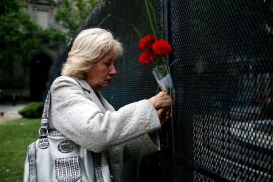 Una mujer deposita un ramo de flores cerca de la Casa de Gobierno. Foto: LA NACION / Silvana Colombo