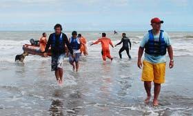 Los tres pescadores, en el momento de llegar a tierra, tras ser rescatados por hombres de la Prefectura.