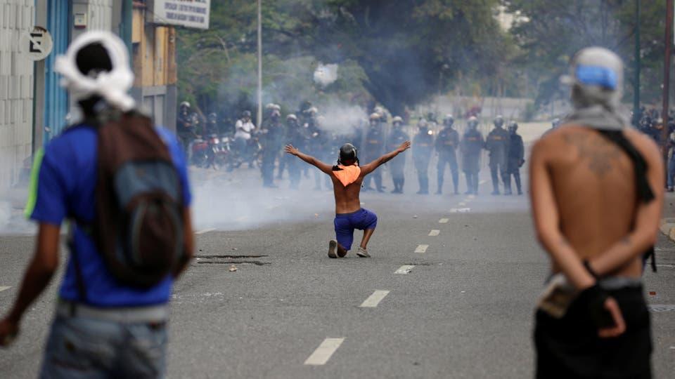 Un joven enfrenta a un decena de pilocías. Foto: Reuters / Marco Bello