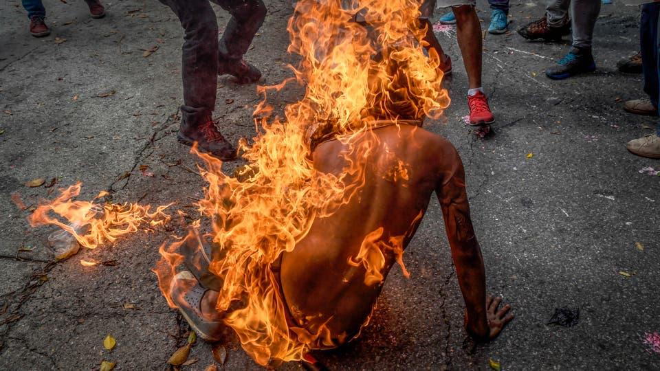 Un manifestante en llamas luego de que el tanque de combustible de una moto de la policía explotara a su lado. Foto: AFP / Juan Barreto