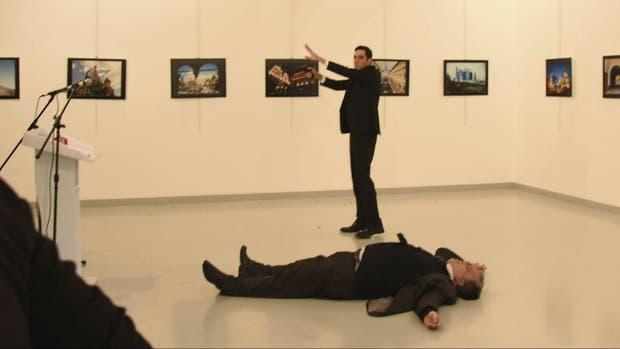 El embajador ruso Karlov yace muerto en el piso, mientras su asesino proclama por la víctimas de la guerra siria